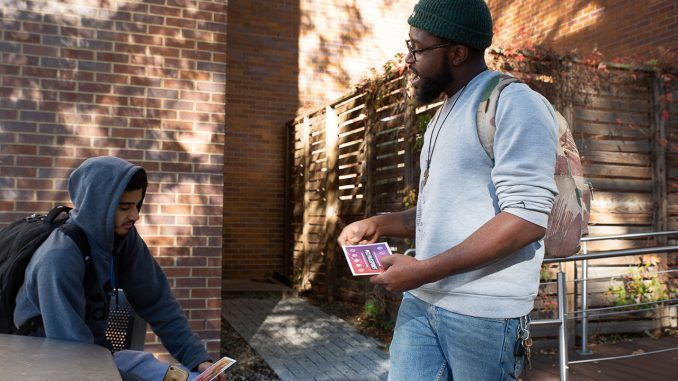 Donnell Powell, Temple University PEX Passport program coordinator, hands out flyers for the program around campus